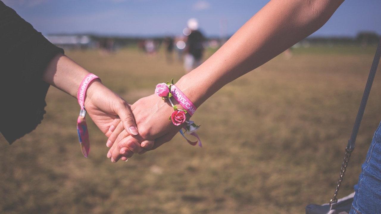 Zwei Frauenhände, die sich halten